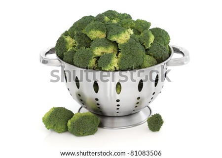 Broccoli vegetable in a stainless steel colander and loose, isolated over white background.