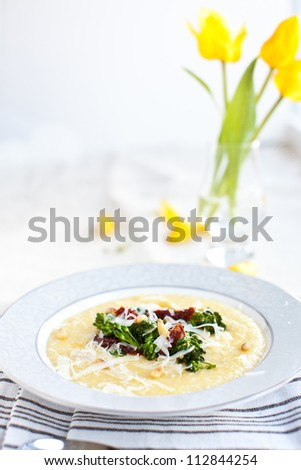 Broccolini with sun-dried tomatoes on a bed of creamy polenta with Parmesan and pine nuts in nice bowl