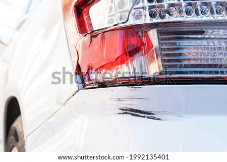 Brocken red taillight without glass and big black scratch on rear bumper due to car accident or careless driving, insurance case, safety driving concept Stockfoto ©