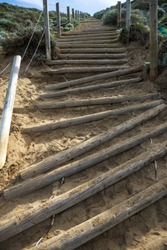 Brocken stairway to ocean beach in Sanfrancisco made on sandy hill with thick wooden logs.