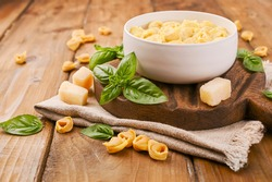 Brodo soup with Tortellini mignon on a wooden board with basil and parmesan. Specialties of the cuisine from Bologna and Emilia Romagna: Cappelletti, fresh egg pasta with meat and vegetables filling.
