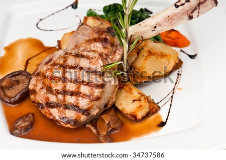 Broiled center cut veal chop with sauteed onions and mushrooms. - stock photo