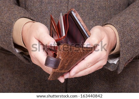 Broke businessman showing brown leather empty wallet. Business concept- finance and poor economy. Stock photo ©