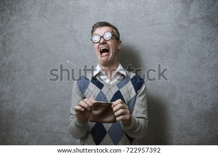 Broke man with thick glasses holding an empty purse and crying, poverty and debts concept