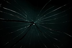 Broken and cracked glass with hole on a black background