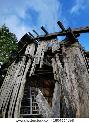 Broken and dilapidated wooden house with blue sky background. ironic view of ruined house. Ruin in abstract.  Stok fotoğraf ©