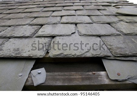 broken and fallen slate leaves hole in a roof due to storm or decay
