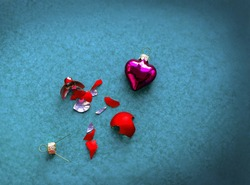 Broken and unbroken heart ornaments on blue background