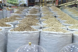 Broken and unbroken pistachios stand side by side in sacks in the shop