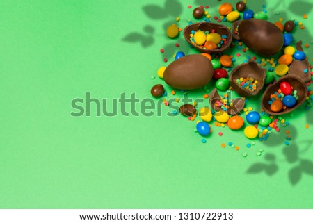 Broken and whole chocolate Easter eggs, multicolored sweets on a green background. Shrub. Concept of celebrating Easter, Easter decorations. Flat lay, top view. Copy Space. #1310722913