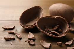 Broken and whole chocolate egg on wooden table, closeup