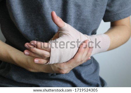 Broken arm concept. Cast broken arm for immobilize after arm and hand injury. Hand wrapped in bandage ストックフォト ©
