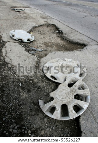 broken asphalt pavement resulting in a pothole, dangerous to motorists.