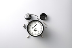 broken black alarm clock on grey background with copy space , time and wilted concept