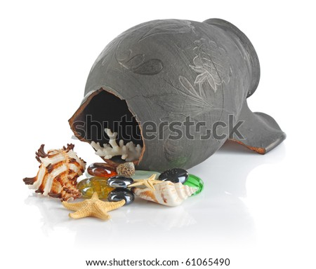 Broken black amphora with seashells and stones on white background