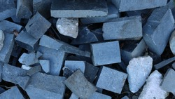 broken blocks and broken stones of different shapes and sizes in a heap of construction debris as a gray material stone background