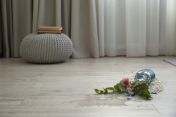Broken blue glass vase and bouquet on floor in room. Space for text