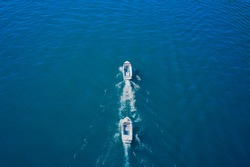 Broken boat in tow in motion on the water, aerial view of the boat