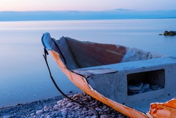 Broken boat laying on a stone beach next to calm ocean with an cloudy sunset as background, at the island of Gotland in Sweden