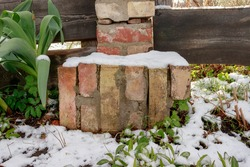 Broken brick fence pole with snow in spring. Wood fence, green plants, grass, flowers, white snow on top. Sunny day. red and yellow bricks and rocks