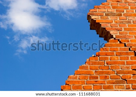 Broken brick wall against the blue sky