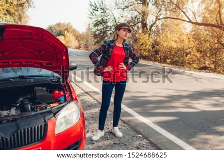 Broken car. Sad woman standing on road by her auto with hood open stopping autos and waiting for help #1524688625