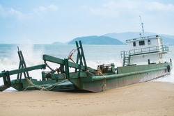 broken cargo ship on the beach in bad weather in Nha Trang Vietnam Southeast Asia with beautiful views of the sea and mountains