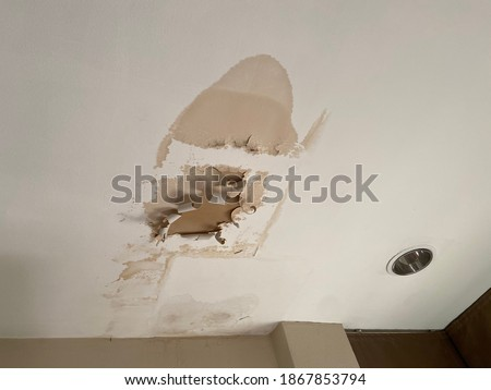 Broken ceiling problem in house because rain water damage in raining season. Ceiling panels damaged huge hole in roof from rainwater leakage.