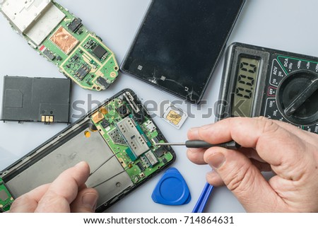 Broken cell phone repair. Smartphone parts and tools for recovery, selective focus