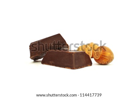 Broken chocolate and hazelnut on white background