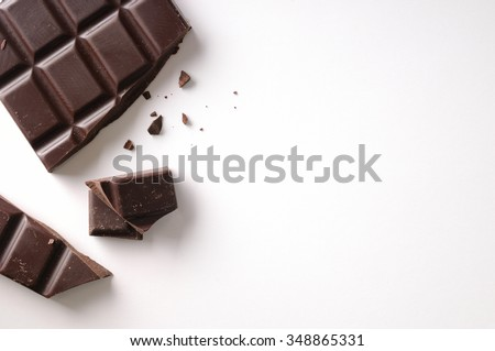 Broken chocolate bar left position isolated on white table. Horizontal composition. Top view