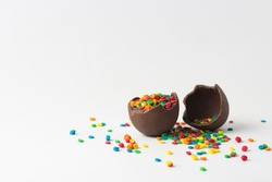 Broken Chocolate Easter egg with multi-colored candy decorations. Copy space