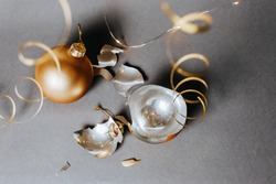 Broken christmas toy to decorate the new year holidays with ribbons and lights on a dark gray background