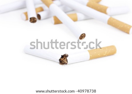 Broken cigarette and some cigarettes on background