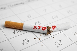 Broken cigarette with word Stop on calendar sheet. Quitting smoking concept