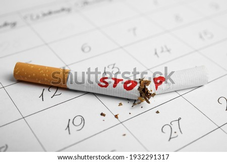 Broken cigarette with word Stop on calendar sheet. Quitting smoking concept Сток-фото ©