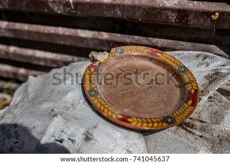 Broken clay plate near a trash dumpster in Armenia #741045637