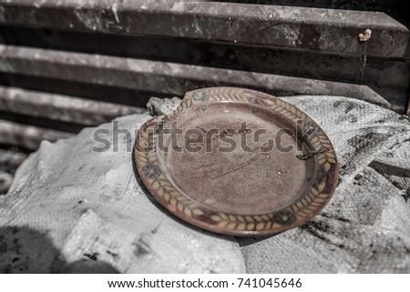Broken clay plate near a trash dumpster in Armenia #741045646