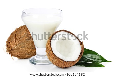 Broken coconut with juice in glass isolated on white - stock photo