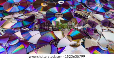 Broken compact discs. Colorful texture detail of obsolete digital media. Data backup, archiving or eco disposal. Old damaged optical storage devices on e-waste heap. Rainbow reflection on shiny disks. #1523635799