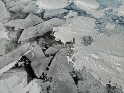 broken cracked Ice hummocks. footprints from fishermen on the snow. winter fishing. snow dunes. Dangerous. Nice pattern background. Aerial view from top down. drone view. Flying over.