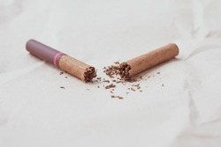 Broken dark cigar on a neutral paper background. Healthy lifestyle concept. A crushed cigarette and scattered tobacco. Copy, text space. Bad habit, nicotine addiction. World no tobacco day.