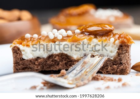 broken divided tartlet with milk cheese filling and lots of salted caramel with nuts, almonds on tartlets with cottage cheese or butter cream and caramel, delicious desserts during meals
