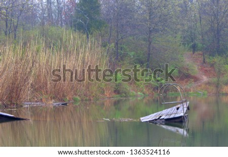 Broken dock in pond. Fits themes for lonely, forgotten, reflection, dilapidated, weathered.