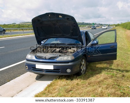 Broken down car on the side of a busy road
