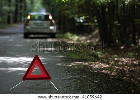 broken down car with warning triangle behind it waiting for assistance to arrive (shallow depth of field, the focus is on the triangle, the car is out of focus)