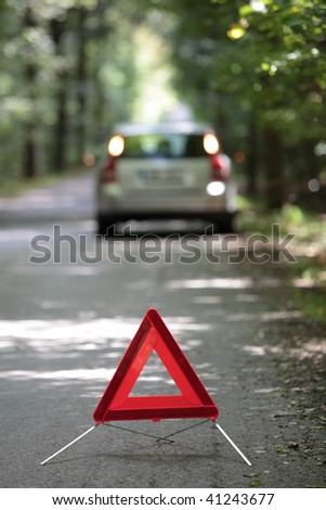 broken down car with warning triangle behind it waiting for assistance to arrive (shallow depth of field, the focus is on the triangle, the car is left out of focus) - stock photo