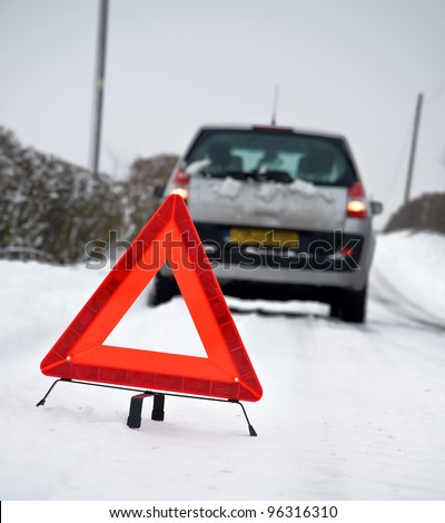 Broken down vehicle in winter snow conditions with red warning triangle