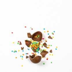 Broken Easter chocolate egg and colorful decorations on a light background. Easter concept, easter treats. Square. Flat lay, top view