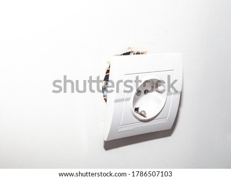 Broken electric socket torn from wall. Fixing loose electrical outlet box on white backhround Сток-фото ©